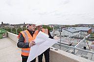 Two men with plan wearing safety vests talking on construction site - DIGF02515