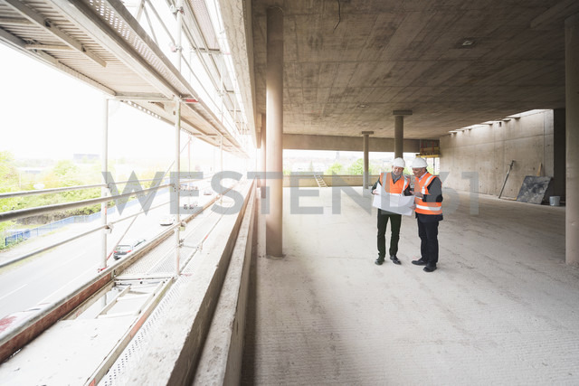 Two men with plan wearing safety vests talking in building under construction - DIGF02518
