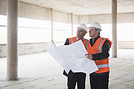 Two men with plan wearing safety vests in building under construction - DIGF02521