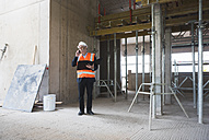 Man on the phone wearing safety vest in building under construction - DIGF02524