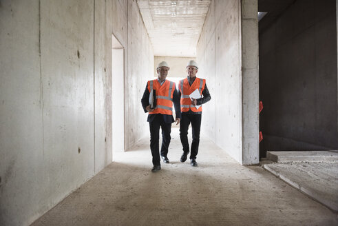 Two men wearing safety walking in building under construction - DIGF02527