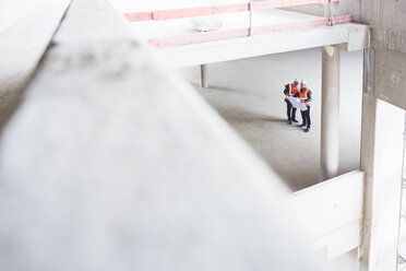 Two men with plan wearing safety vests talking in building under construction - DIGF02530