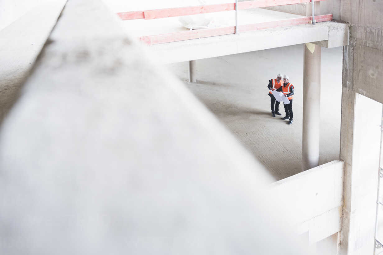 Two men with plan wearing safety vests talking in building under construction - DIGF02530 - Daniel Ingold/Westend61