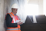Man with tablet wearing safety vest in building under construction - DIGF02533