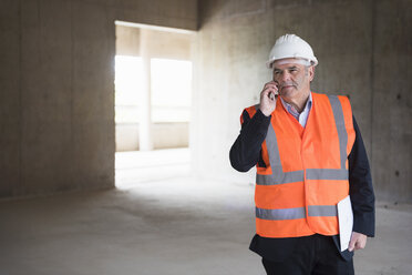 Man on the phone wearing safety vest in building under construction - DIGF02539