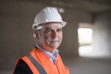 Portrait of man wearing safety vest in building under construction - DIGF02542