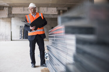 Man with documents wearing safety vest in building under construction - DIGF02545