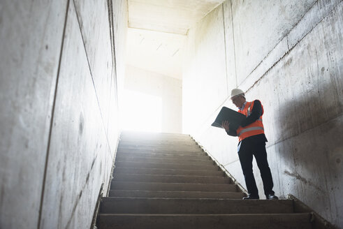 Man with documents wearing safety vest in building under construction - DIGF02548