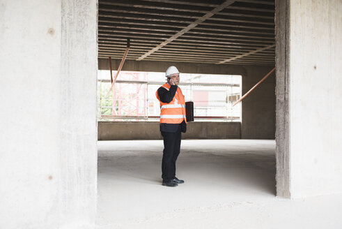 Man on the phone wearing safety vest in building under construction - DIGF02551