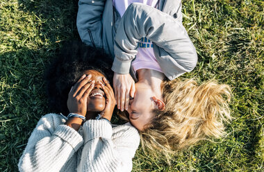 Two best friends telling secrets lying in the grass - MGOF03339