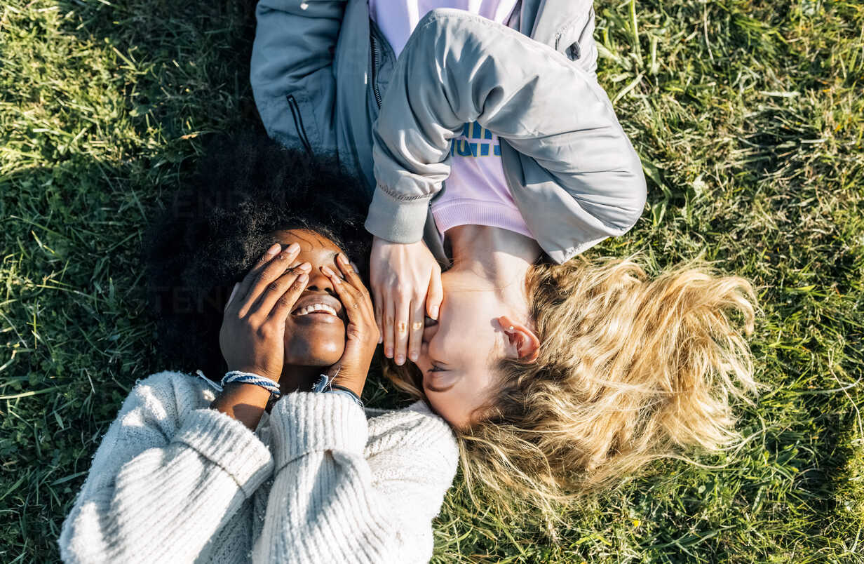 Two best friends telling secrets lying in the grass - MGOF03339 - Marco Govel/Westend61