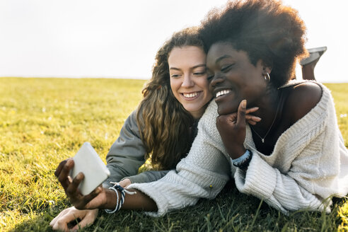 Two best friends lying in grass with cell phone - MGOF03342