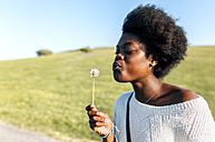 Young woman blowing a dandelion - MGOF03348