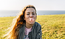 Teenage girl making a gum bubble outdoors - MGOF03357