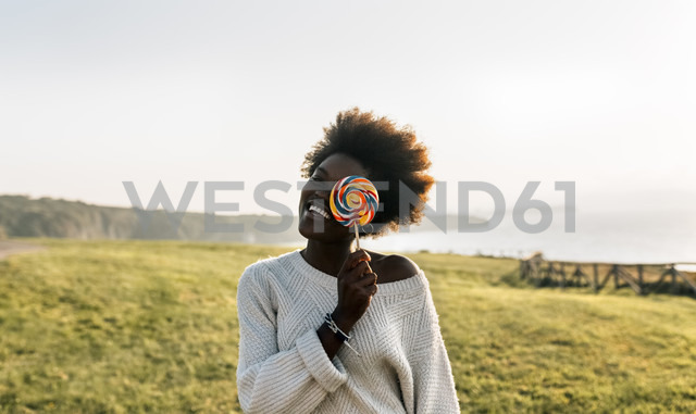 Young woman having covering eye with a lollipop, laughing - MGOF03372