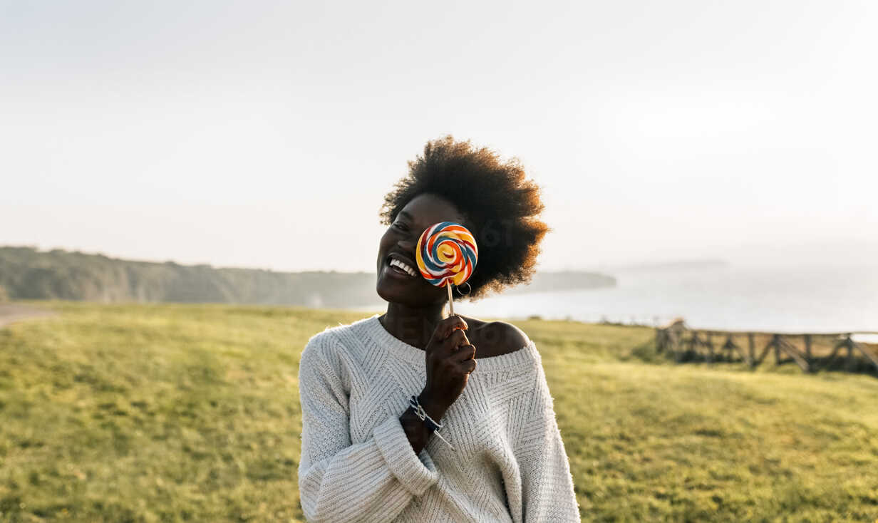 Young woman having covering eye with a lollipop, laughing - MGOF03372 - Marco Govel/Westend61