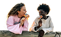 Two best friends eating lollipops outdoors - MGOF03375