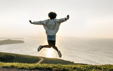 Young woman jumping at the coast at sunset - MGOF03387