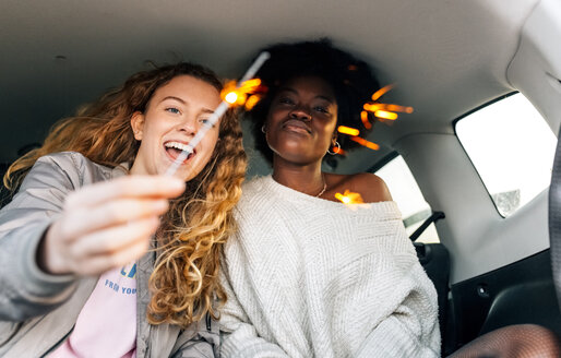 Two best friends sitting in a car playing with sparklers - MGOF03393
