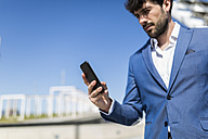 Young businessman looking at smartphone outdoors - GIOF02568