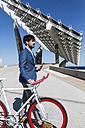 Young businessman with fixie bike and smartphone outdoors - GIOF02571