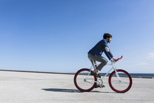 Young businessman on fixie bike outdoors - GIOF02574