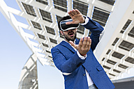 Young businessman wearing VR glasses outdoors - GIOF02577