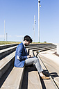 Young businessman sitting on stairs using laptop - GIOF02580