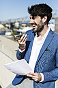 Happy young businessman with smartphone and documents outdoors - GIOF02586