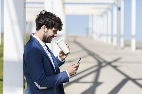 Happy young businessman with smartphone and takeaway coffee outdoors - GIOF02592
