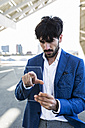 Young businessman using futuristic portable device - GIOF02595