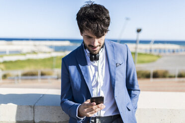 Young businessman looking at smartphone outdoors - GIOF02601