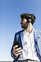 Young businessman with smartphone wearing headphones under blue sky - GIOF02604