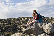 Spain, Madrid, young woman resting on a rock using her phone during a trekking day - ABZF01999