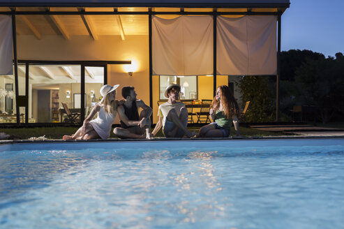 Four friends relaxing at the poolside at evening twilight - ZOCF00301