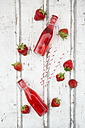 Three glass bottles of homemade strawberry lemonade and strawberries on white wood - LVF06106