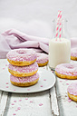 Doughnuts with pink icing and sugar granules and a bottle of milk - LVF06112