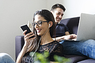 Young woman on the phone in the living room with boyfriend on the couch in the background - FMOF00278