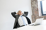 Mature businessman sitting in office with hands behind head - FMKF04080