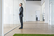 Mature businessman standing in office space with green grass carpet - FMKF04116