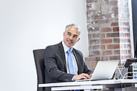 Mature businessman sitting in office, smiling - FMKF04134