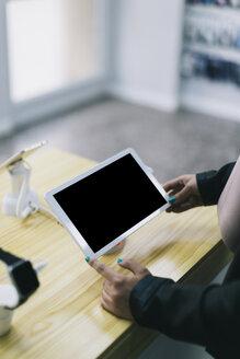 Customer choosing tablet in shop - JPF00198