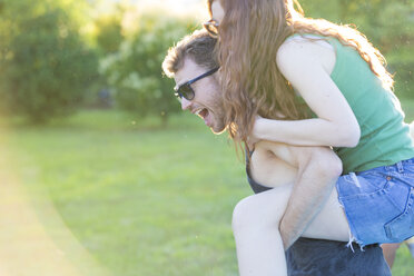 Young man giving his girlfriend a piggyback ride in the garden - ZOCF00350