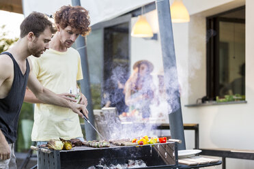 Two men at barbecue grill - ZOCF00353