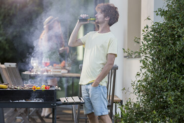 Man having a beer at barbecue grill - ZOCF00356