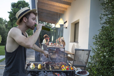Man having a beer at barbecue grill with friends in background - ZOCF00359