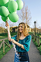 Portrait of laughing young woman with green balloons - DAPF00754