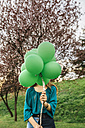 Young woman hiding behind green balloons - DAPF00763