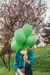 Young woman hiding behind green balloons - DAPF00763