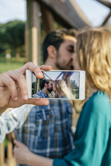 Kissing young couple taking selfie with smartphone - DAPF00765